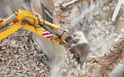 Excavator bucket in dust cloud during building demolition.